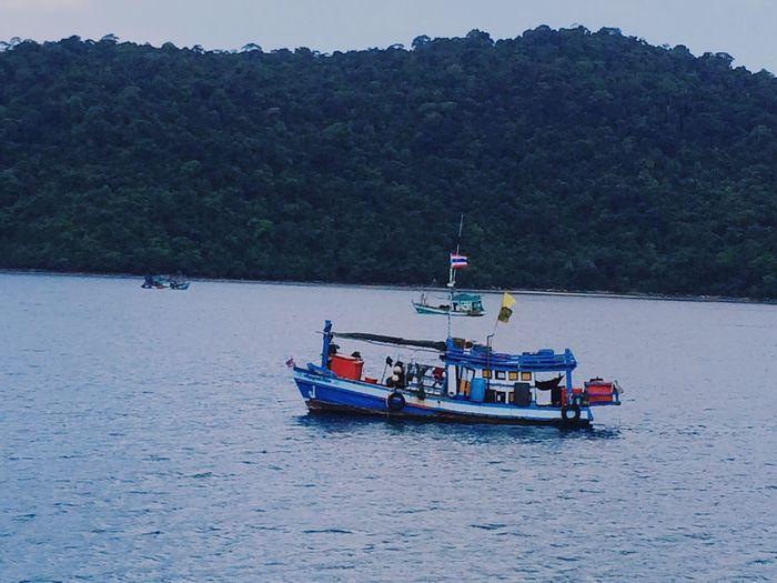 Thai fishing boats floating on the sea. Thai Fishing Boat Boat Floating Sea Boats Beauty In Nature Mountain And Sea Scene