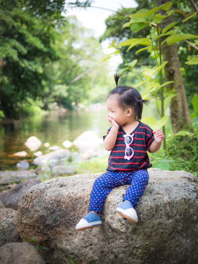 child girl scared sitting on a rock with river on the background Asian Girl Casual Clothing Child Childhood Cute Day Full Length Hairstyle Innocence Leisure Activity Lifestyles Nature One Person Outdoors Real People Rock Rock - Object Scared Sitting Solid Tree Women