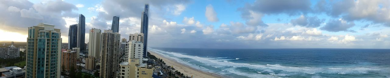 Panoramic View Of Buildings By Beach Against Cloudy Sky