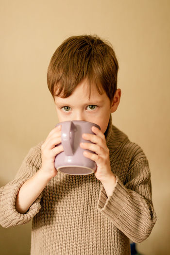 Boy drinks cocoa. warm autumn photography. a boy in a brown sweater drinks from a mug.