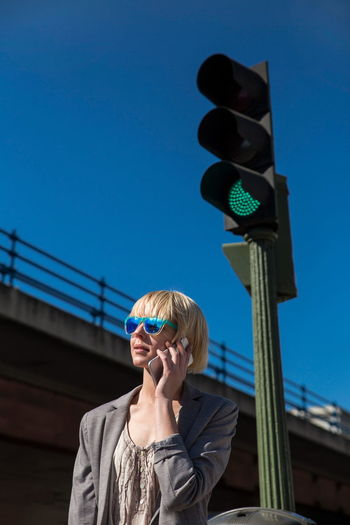 Low angle view of person wearing sunglasses against sky