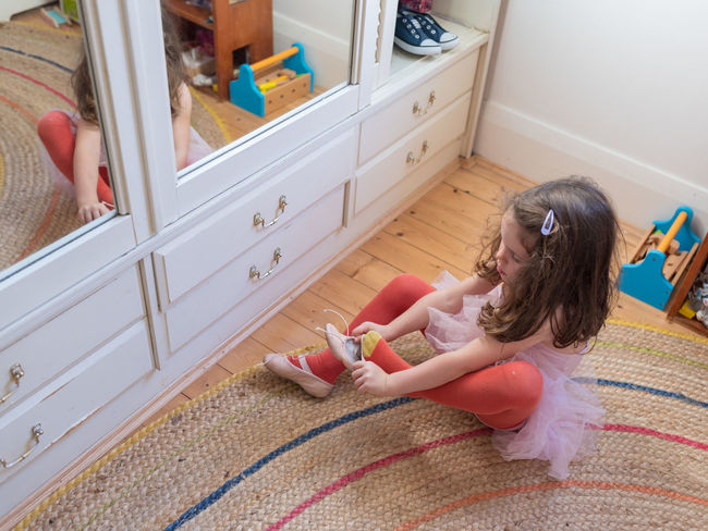 Little girl in bedroom putting on ballet shoes Casual Clothing Child Childhood Females Flooring Full Length Furniture Girls Hairstyle High Angle View Home Interior Indoors  Innocence Leisure Activity Lifestyles One Person Playing Real People Representation Toy Women