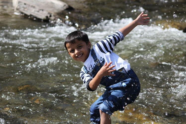 Portrait of happy boy enjoying in water