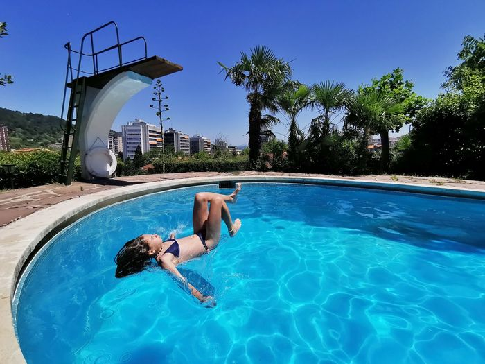 Man relaxing in swimming pool against blue sky