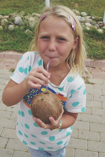Close-up portrait of girl drinking coconut water