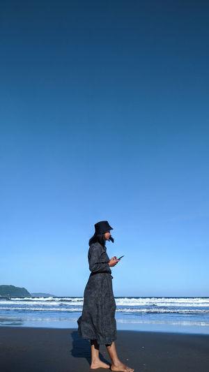 Full length of girl on beach against clear blue sky