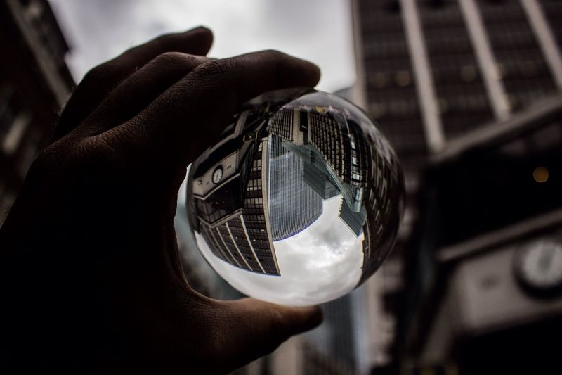 Cropped image person hand holding crystal ball against buildings in city