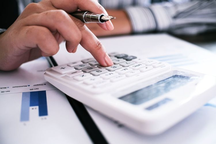 Cropped Image Of Businesswoman Using Calculator In Office