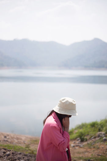 Side view of woman in hat by lake against sky