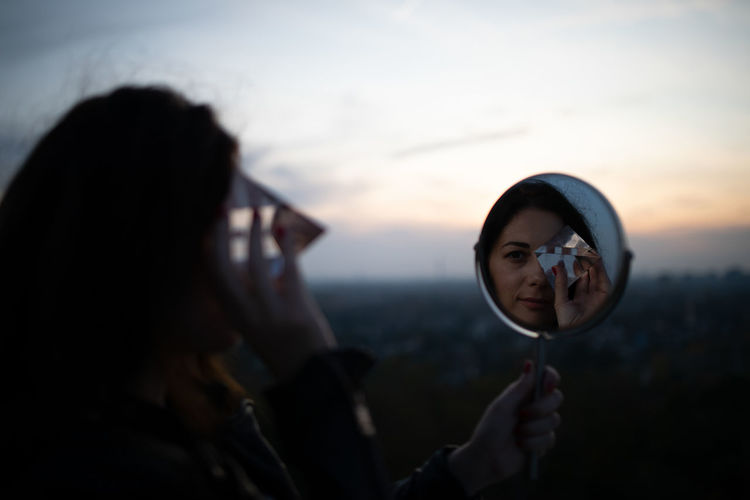 Reflection of woman holding prism in mirror against sky during sunset