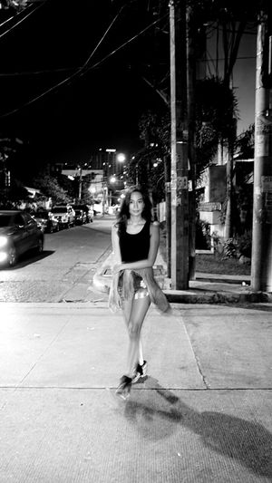 Full length rear view of woman standing at night