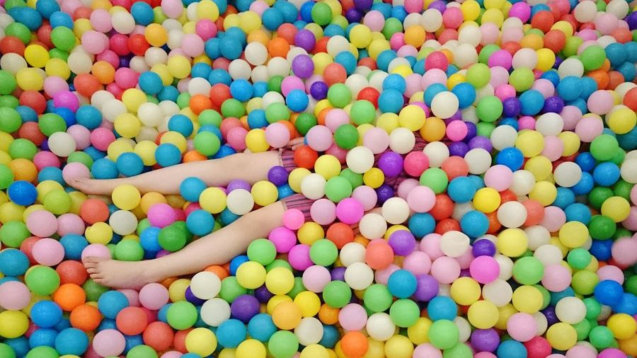 Person buried under colorful balls
