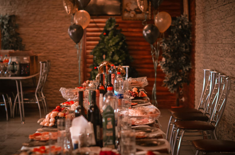 Holiday Feast Festive Table Celebratory Table Table With Food Furniture Large Group Of Objects Arrangement Place Setting Dining Table Celebration Drinking Glass Chair Food And Drink Selective Focus Wineglass Table Setting Decoration Glass Absence Luxury No People