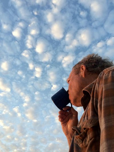 Low Angle View Of Man Drinking Coffee Against Sky