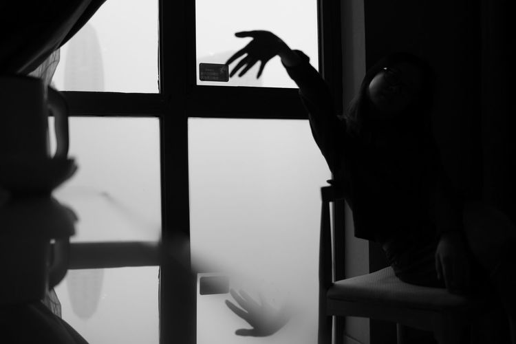 Cropped hand by window