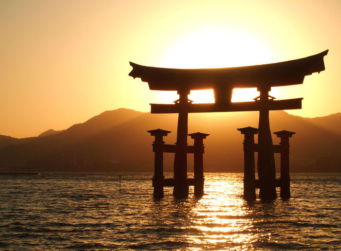 Silhouette torii gate amidst river against sky during sunset
