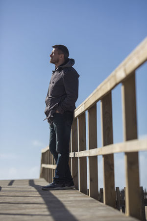 Man standing on boardwalk. Masculinity Standing Adolescence  Boardwalk Casual Clothing Clear Sky Contemplation Full Length Leisure Activity Lifestyles Looking Looking Away Low Angle View One Person Real People Side View Sky Sunlight Wooden Young Adult