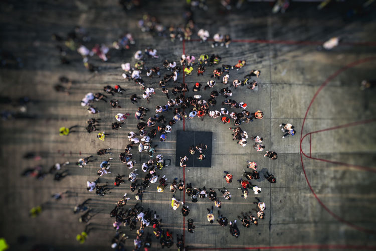 Drone, high angle view from above of people gathering, walking on city street