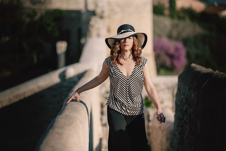 Portrait Of Mature Woman Wearing Hat While Standing Amidst Wall