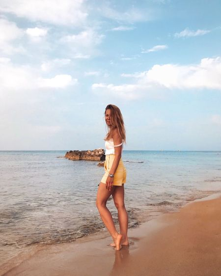 Full length of young woman on beach against sky