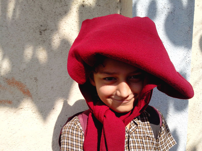 Portrait Of Schoolboy With Red Sweater On Head Against Wall