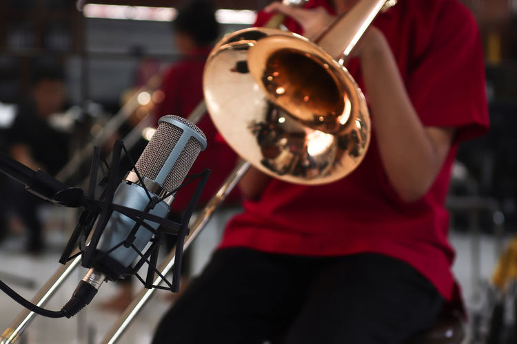 Microphone on Trombone background Music Microphone Arts Culture And Entertainment Input Device Performance Musical Instrument Musician Focus On Foreground Artist Incidental People Performing Arts Event Musical Equipment Occupation People Clothing Close-up Men Skill  Red Stage