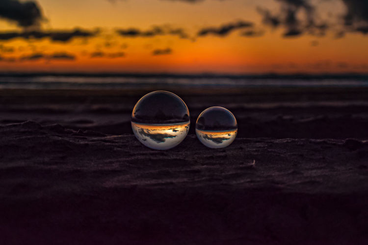 Close-up of sunglasses on beach during sunset
