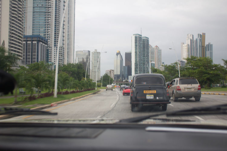 Cars on road by buildings in city against sky