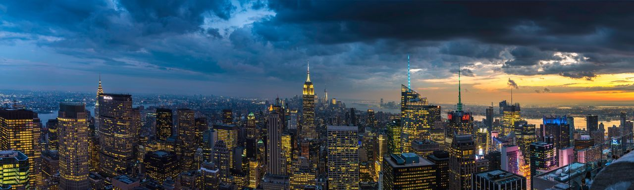 Panoramic view of illuminated cityscape against dramatic sky