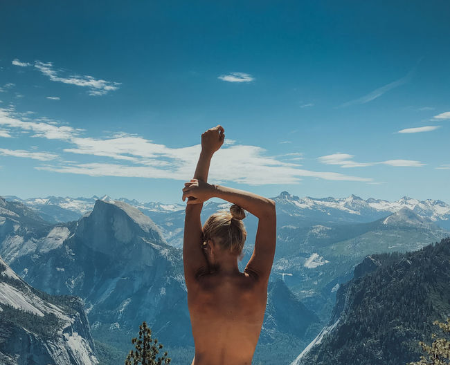 Rear view of shirtless woman against mountains and sky