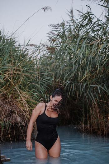 Cheerful woman wearing black swimsuit standing in lake
