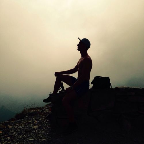 Low angle view of silhouette man sitting on landscape against sky