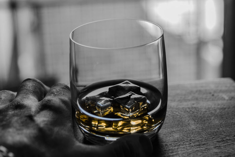 Close up point of view whiskey on ice drink in hand on bar counter, selective color amber and black and white. Amber Premium Relaxing Addiction Alcohol Bourbon Business Finance And Industry Close-up Day Drink Drinking Glass Focus On Foreground Food And Drink Freshness Hand Health Human Element Indoors  Masculine Mental No People Scotch Selective Color Table Whiskey