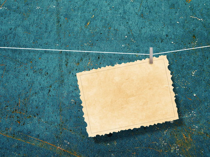 Close-Up Of Paper Hanging Against Weathered Wall
