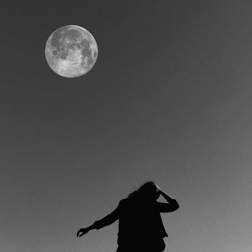 Low Angle View Of Woman Against The Moon