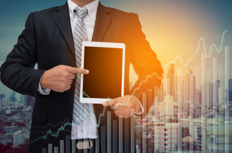 Double exposure of businessman pointing at digital tablet with bar graph against city