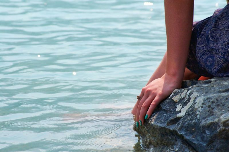 Midsection of woman sitting on rock in sea