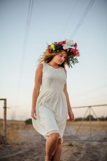 Woman wearing flowers walking on field against sky
