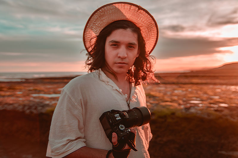 Portrait Of Man In Hat Holding Camera Against Sky During Sunset