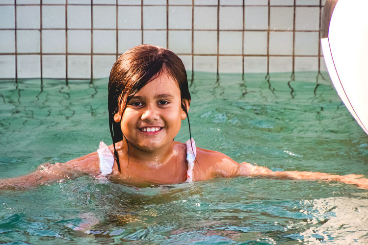portrait of a happy young girl in the pool Water Leisure Activity Portrait Smiling Headshot Swimming Lifestyles One Person Looking At Camera Swimming Pool Real People Happiness Front View Nature Pool Day Waterfront Emotion Outdoors Turquoise Colored Diversity Girls Vacations