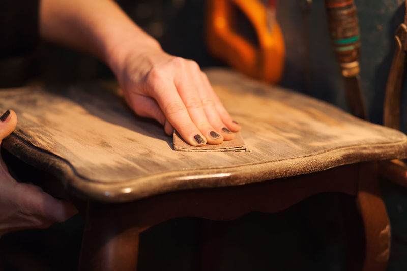 Close-up of woman sanding furniture with sand paper