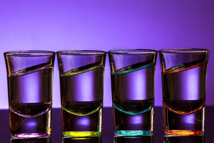 Shot glasses arranged side by side on table