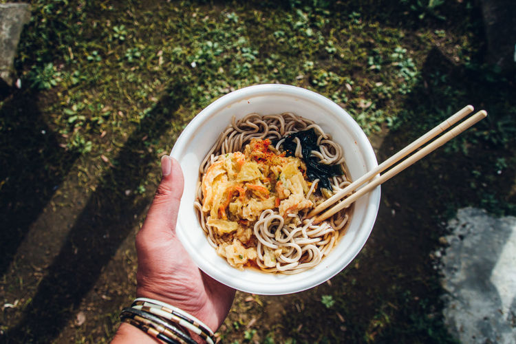 Directly above of eating soba noodles in the yard in japan / personal perspective