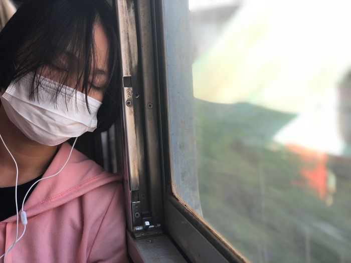 Woman wearing mask while listening music in train