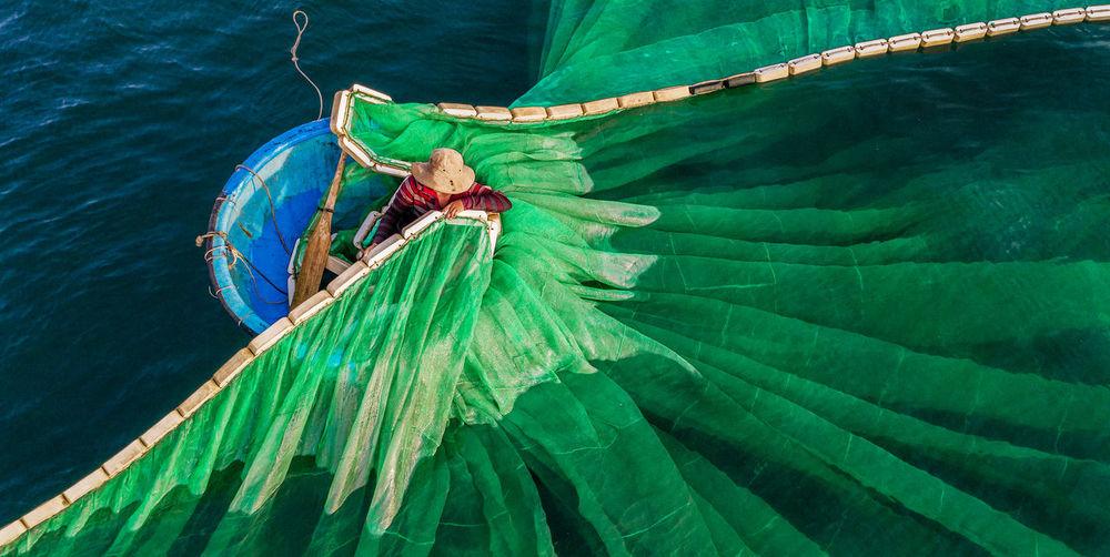 Drone shot of fisherman putting fishing net in sea