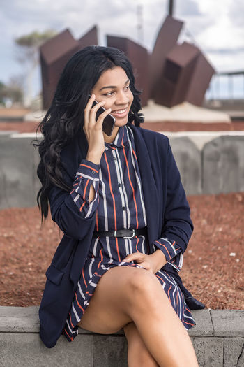 Smiling businesswoman talking on phone while sitting outdoors