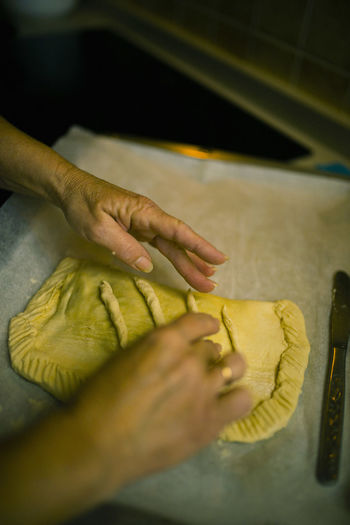 Cropped image of woman with dough on cutting board