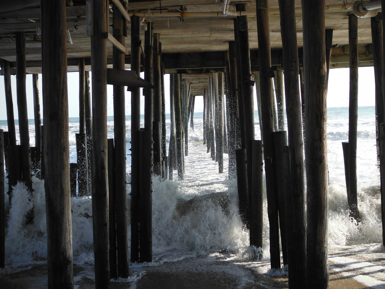 underneath, sea, architectural column, in a row, water, pier, beach, day, architecture, nature, built structure, no people, below, indoors