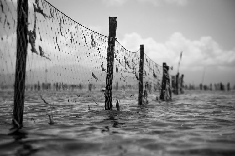 Close-up of net in water against sky