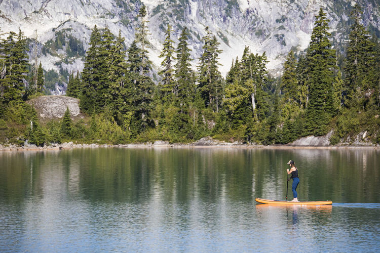 Man surfing in lake against trees in forest